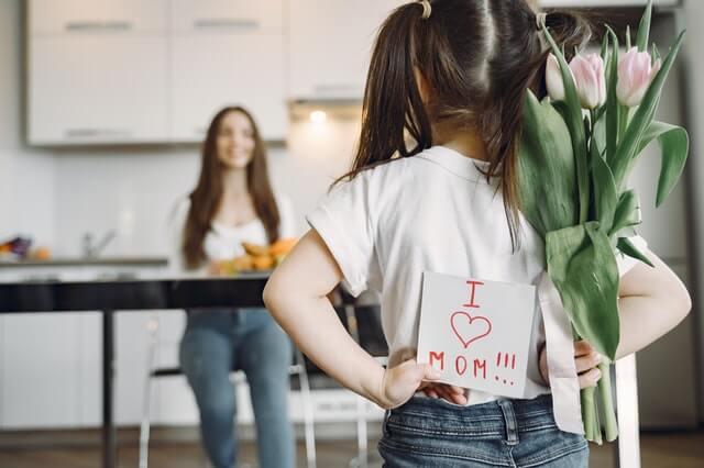 Dziewczynka z kwiatami i kartką walentynkową dla mamy. Pomysł na walentynki z dziećmi.