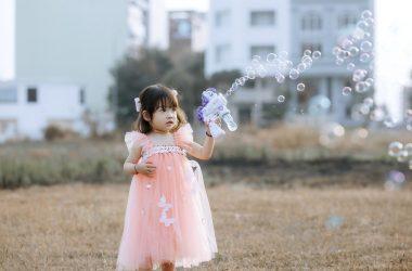 sukienki dla dziewczynek na wesele - mała dziewczynka w sukience księżniczki puszcza bańki mydlane