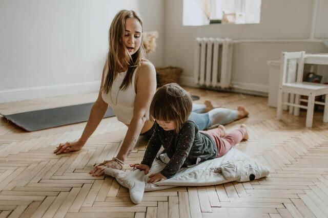 Trening dla dziecka w domu. Kobieta ćwiczy z małym dzieckiem.