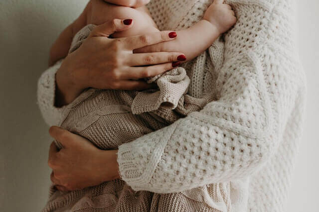 Kobieta trzyma swoje dziecko. Trudne macierzyństwo.